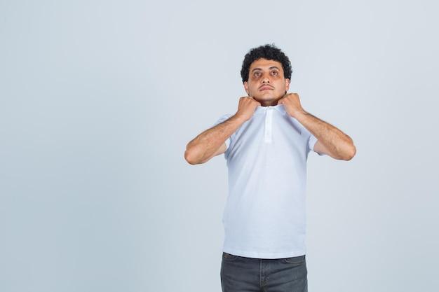 Jonge man trekt kraag van zijn t-shirt in wit t-shirt, broek en kijkt angstig. vooraanzicht.