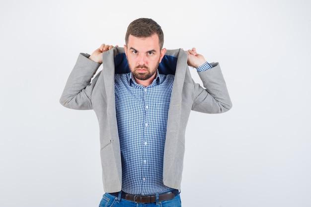 Jonge man trekt revers van jas terwijl poseren in shirt, spijkerbroek, colbert en op zoek ernstig, vooraanzicht.