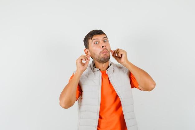 Jonge man trekt zijn oorlellen in t-shirt, jasje naar beneden en kijkt verward