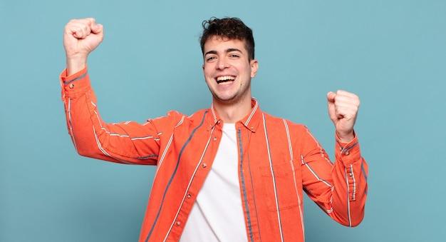 Jonge man triomfantelijk schreeuwend, eruitziend als een opgewonden, blije en verraste winnaar, vierend