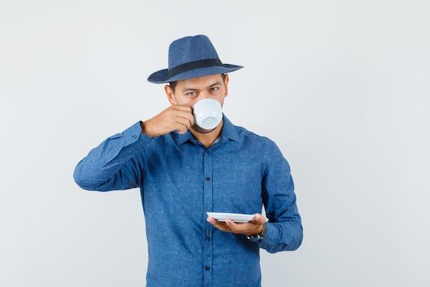 Jonge man turkse koffie drinken in blauw shirt, hoed vooraanzicht.