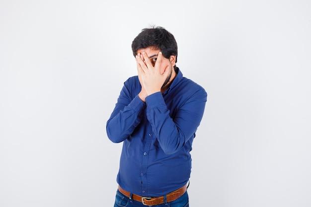 Jonge man tuurt naar buiten met één oog tussen zijn vingers in shirt, spijkerbroek en ziet er verstandig uit.