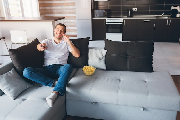 Jonge man tv kijken in zijn eigen appartement. gelukkig opgewonden man praten over de telefoon en het gebruik van de afstandsbediening voor het schakelen van tv-kanalen