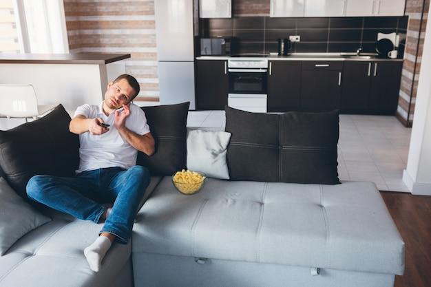 Jonge man tv kijken in zijn eigen appartement. praten over de telefoon en tegelijkertijd de afstandsbediening gebruiken voor tv. movieholic schakelkanalen. alleen plezier in de kamer. moderne technologieën. telefoongesprek.