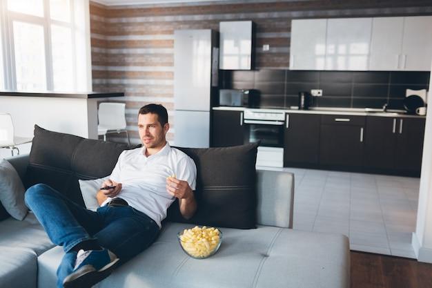 Jonge man tv kijken in zijn eigen appartement. zit alleen op de bank en eet snacks. gebruik de afstandsbediening voor het wisselen van tv-kanalen.