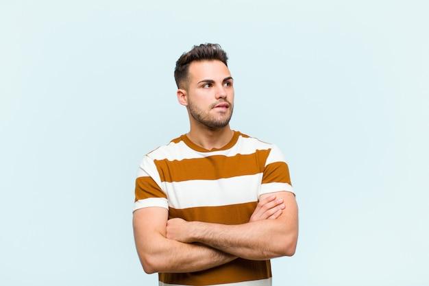 Jonge man twijfelen of denken, lip bijten en zich onzeker en nerveus voelen, op zoek naar ruimte aan de zijkant over de blauwe muur te kopiëren