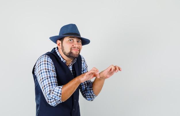 Jonge man typen gebaar met gebalde vingers in overhemd, vest, hoed en geamuseerd op zoek.