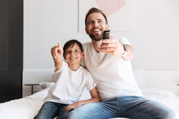 Jonge man vader vader plezier met zijn zoon tv kijken met afstandsbediening.