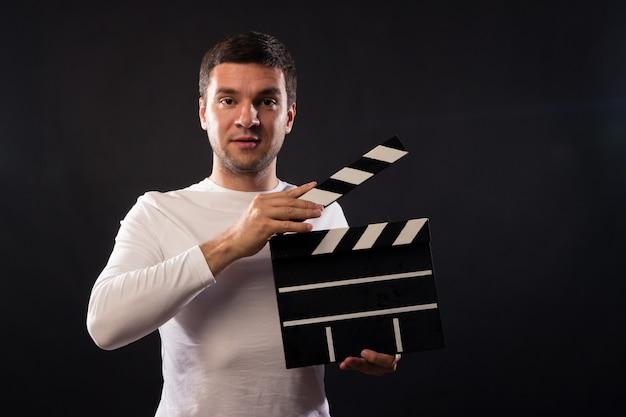 Jonge man van blanke uiterlijk houdt een clapperboard.