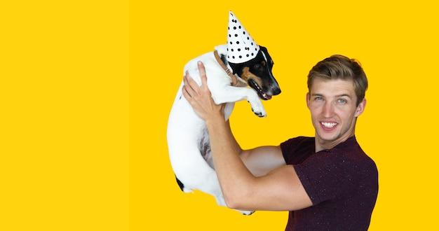 Jonge man van europees uiterlijk op een gele achtergrond. een hond vasthoudend jack russell opstaan