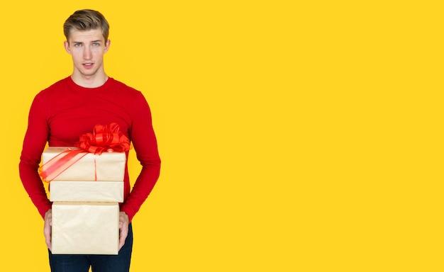 Jonge man van europees uiterlijk op een gele achtergrond. houdt dozen met geschenken. ruimte kopiëren