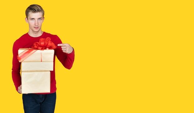 Jonge man van europees uiterlijk op een gele achtergrond. houdt dozen met geschenken vast met een wijsvinger die ernaar wijst.