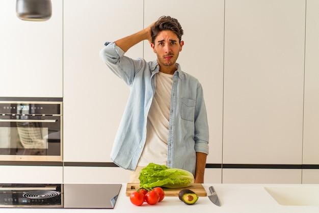Jonge man van gemengd ras die een salade voor de lunch bereidt, geschokt is, herinnert ze zich een belangrijke ontmoeting.
