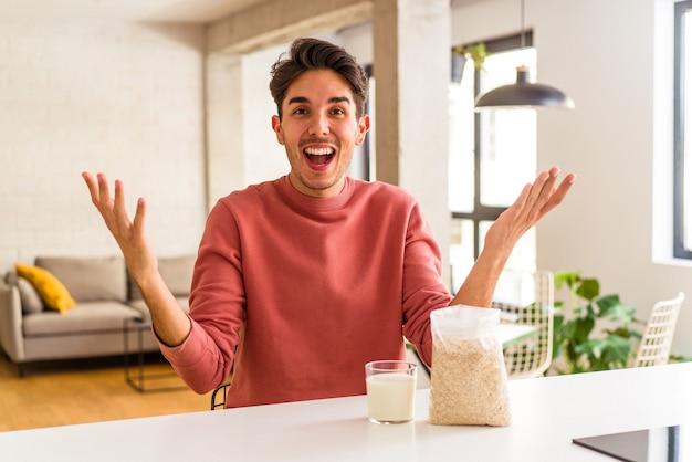 Jonge man van gemengd ras die havermout en melk eet als ontbijt in zijn keuken en een aangename verrassing ontvangt, opgewonden en handen opsteken.