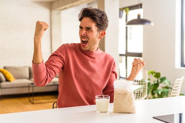 Jonge man van gemengd ras die havermout en melk eet als ontbijt in zijn keuken en vuist opheft na een overwinning, winnaarconcept.