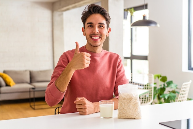 Jonge man van gemengd ras die havermout en melk eet als ontbijt in zijn keuken, glimlachend en duim omhoog