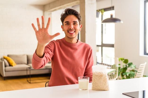 Jonge man van gemengd ras die havermout en melk eet als ontbijt in zijn keuken, vrolijk glimlachend nummer vijf met vingers.