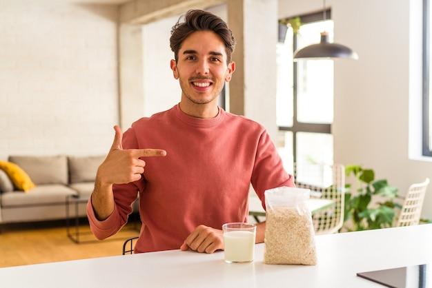 Jonge man van gemengd ras die havermout en melk eet als ontbijt in zijn keukenpersoon die met de hand wijst naar een shirtkopieerruimte, trots en zelfverzekerd