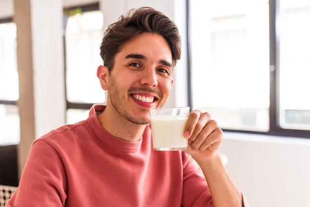Jonge man van gemengd ras die melk drinkt als ontbijt