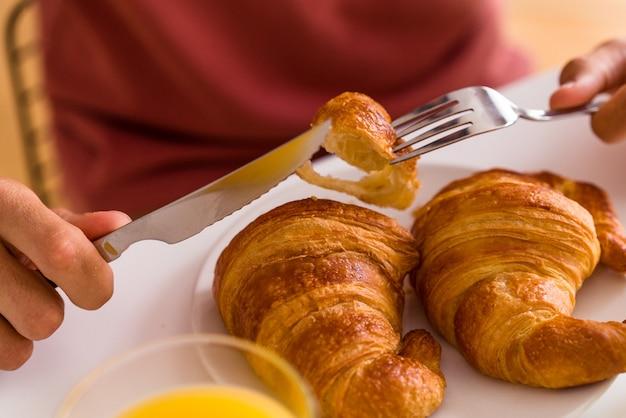 Jonge man van gemengd ras die 's ochtends croissants eet in een keuken