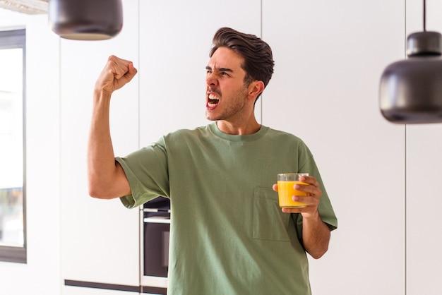 Jonge man van gemengd ras die sinaasappelsap drinkt in zijn keuken die vuist opheft na een overwinning, winnaarconcept