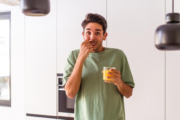 Jonge man van gemengd ras die sinaasappelsap drinkt in zijn keuken en vingernagels bijt, nerveus en erg angstig.