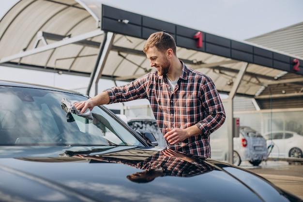 Jonge man veegt zijn auto af na het wassen van de auto