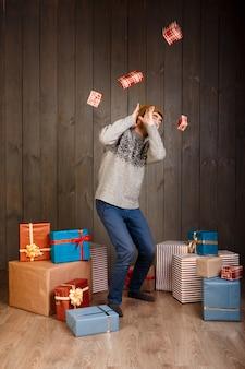 Jonge man verbergen voor vallende kerstcadeaus over houten oppervlak