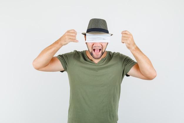 Jonge man verbergt ogen achter medisch masker in groen t-shirt en hoed en ziet er grappig uit