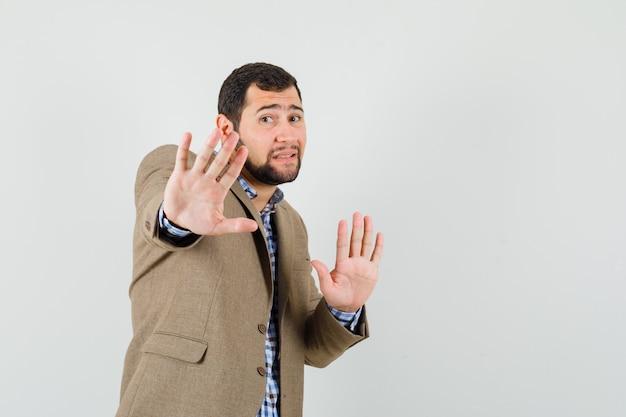 Jonge man verhogen handen op beschermende manier in shirt, jasje en bang op zoek.