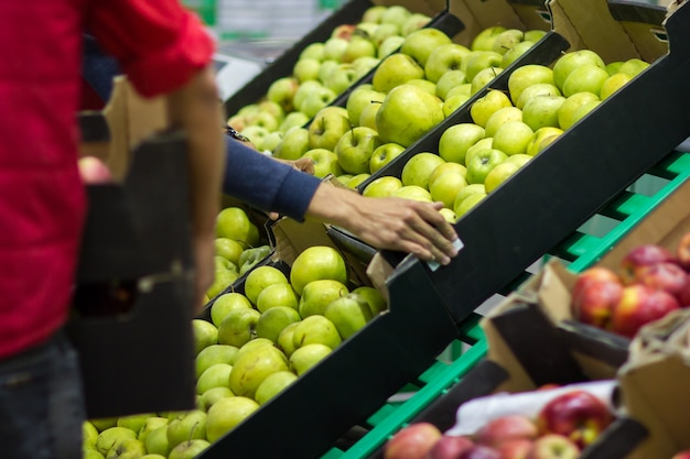 Jonge man verkoper legt vers fruit van de doos op de supermarkt.