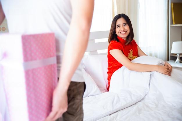 Jonge man verrassing vriendin met heden achter rug