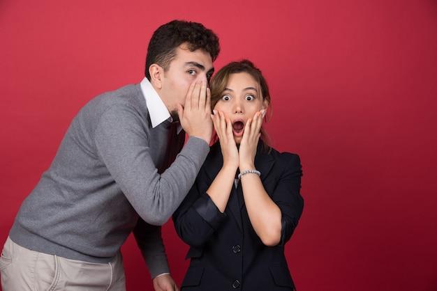Jonge man vertelt een paar geschokte geruchten aan zijn vriendin op een rode muur