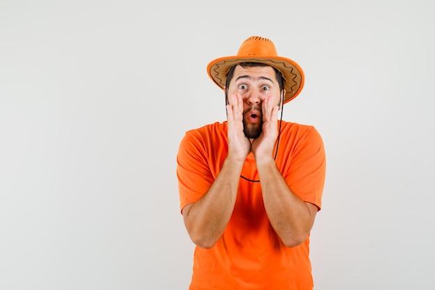 Jonge man vertelt geheim met handen in de buurt van mond in oranje t-shirt, hoed, vooraanzicht.