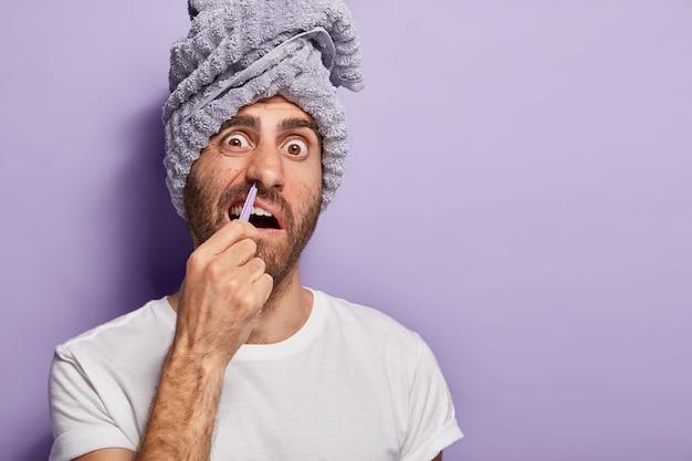 Jonge man verwijdert neushaar met een pincet, grijnst en staart van pijn
