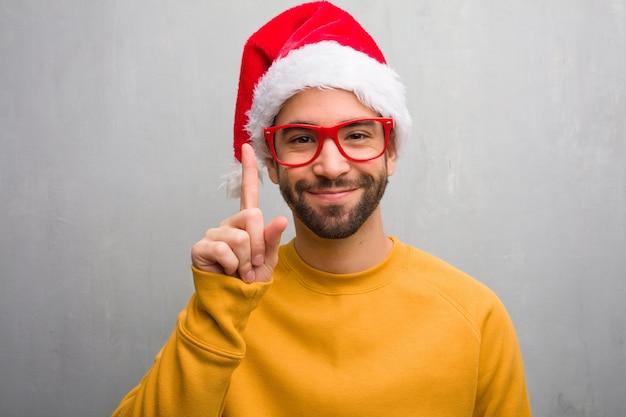 Jonge man vieren kerst dag houden geschenken tonen nummer één