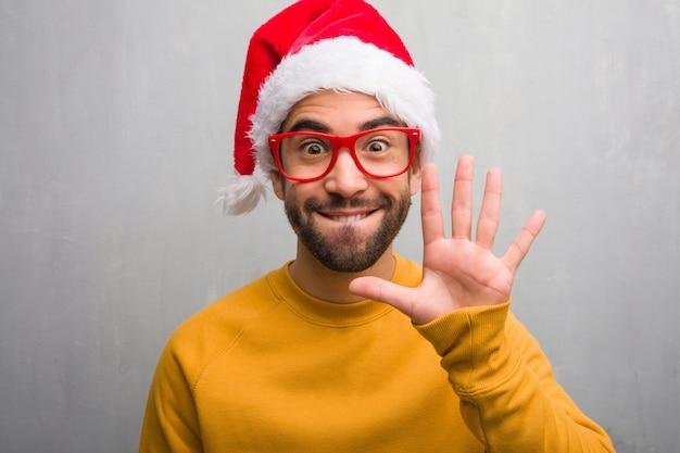 Jonge man vieren kerst dag houden geschenken tonen nummer vijf