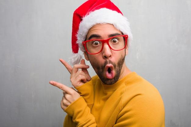 Jonge man vieren kerst dag houden geschenken wijzen naar de kant met de vinger