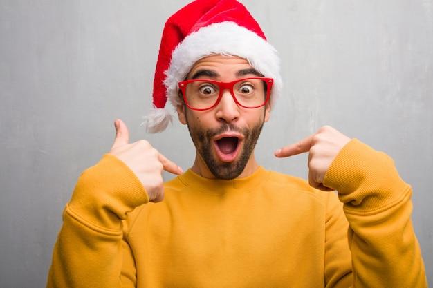 Jonge man vieren kerstdag houden geschenken verrast, voelt zich succesvol en welvarend