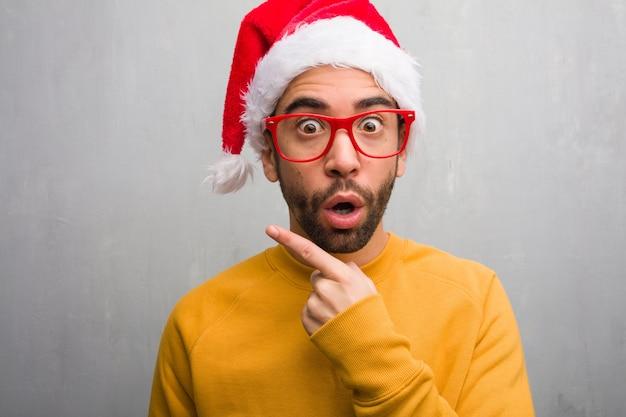 Jonge man vieren kerstdag houden geschenken wijzend naar de kant