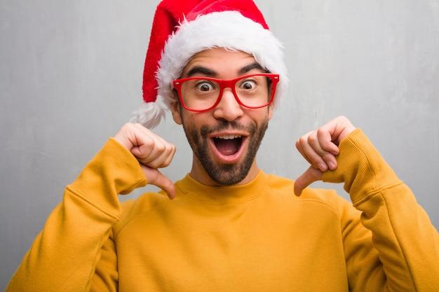 Jonge man vieren kerstdag houden geschenken wijzende vingers, voorbeeld te volgen