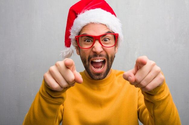 Jonge man vieren van kerstdag houden geschenken vrolijk en glimlachen