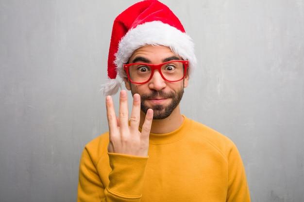 Jonge man viert de giften van de de dagholding van kerstmis die nummer vier tonen