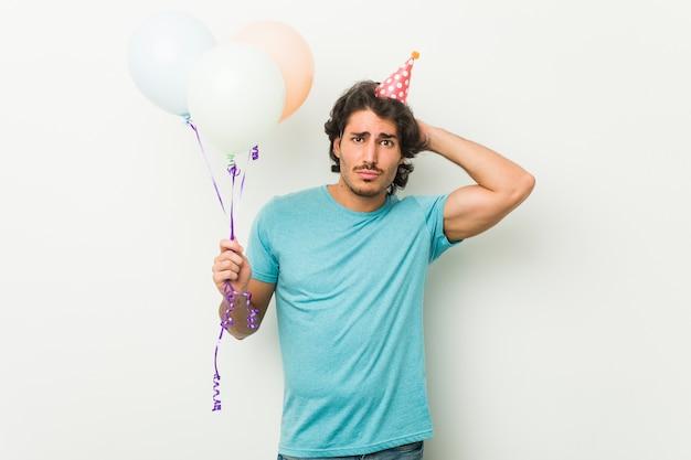 Jonge man viert een feest met ballonnen die geschokt zijn, ze herinnert zich een belangrijke bijeenkomst.
