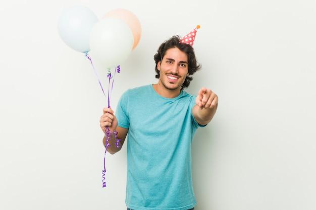 Jonge man viert een feest met ballonnen vrolijke glimlach wijst naar de voorkant.
