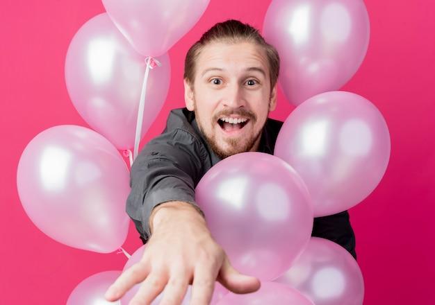 Jonge man viert verjaardagsfeestje met ballonnen verbaasd en verrast over roze