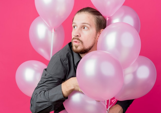 Jonge man viert verjaardagsfeestje met een heleboel ballonnen opzij kijken verrast staande over roze muur
