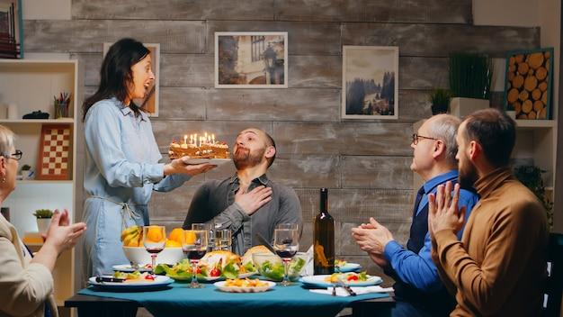 Jonge man viert zijn verjaardag met de familie. diner eten. heerlijke taart. slow-motion opname