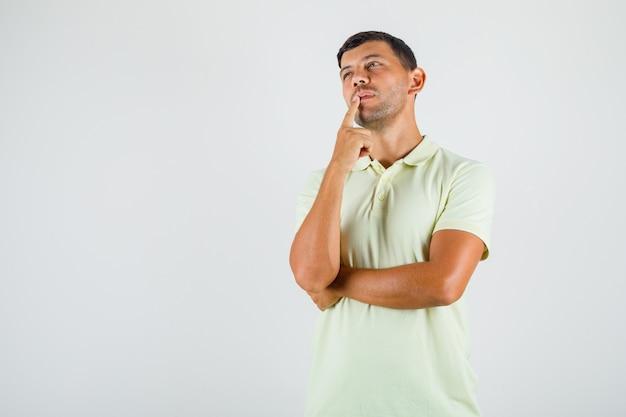 Jonge man vinger prop op mond in t-shirt zetten en op zoek attent