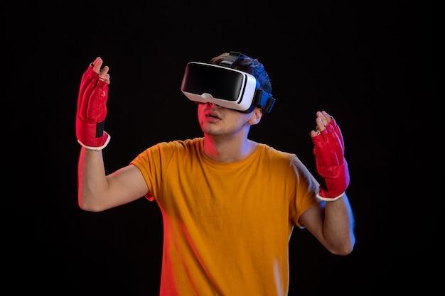 Jonge man virtual reality spelen in mma handschoenen op dark desk gaming d tech visual